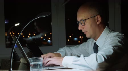 последний : Executive businessman using laptop computer while working overtime in dark office