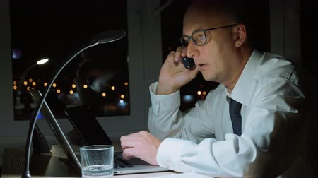 őrlés : Concentrated businessman working on laptop and talking by phone in dark office Stock mozgókép