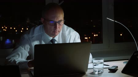 compromisso : Executive manager working with laptop and drinking water in office at night