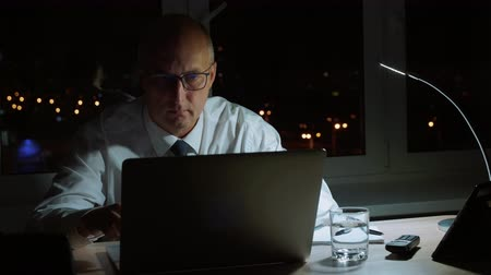 compromisso : Executive businessman wearing glasses and working on laptop at workplace in evening