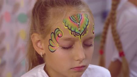 face painting : Face young girl while application multicolor aquagrim with glitter on skin