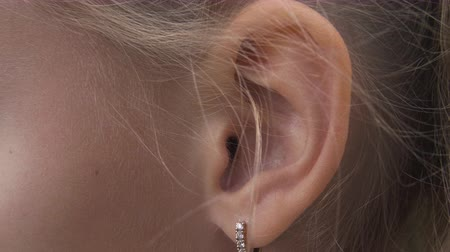 earlobe : Female ear with earring close up. Ear of woman blonde with decorative piercing Stock Footage