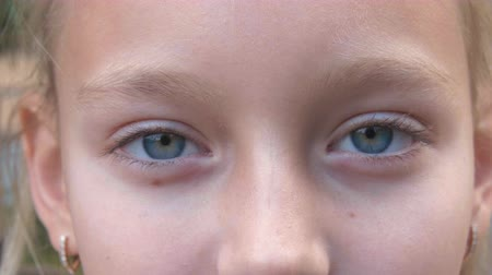 irys : Young girl with closed eyes closeup. Face girl with gray eyes looking in camera Wideo