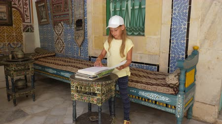 el yazması : Sousse, Tunisia - June 15, 2018: girl looking ancient book in historical art and culture museum in palace in Medina Sussa. Mosaics interior in Arabic architecture. Stok Video