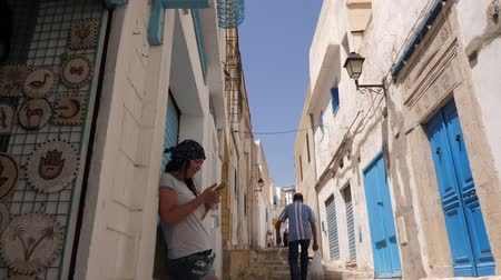 tunezja : Sousse, Tunisia - June 15, 2018. Traveling woman using mobile phone at narrow street in old city