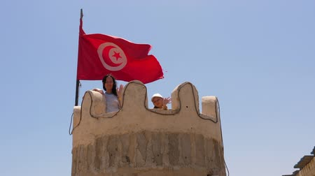 tunisia : Woman and girl waving hands and looking to camera from top of tower with Tunisia flag