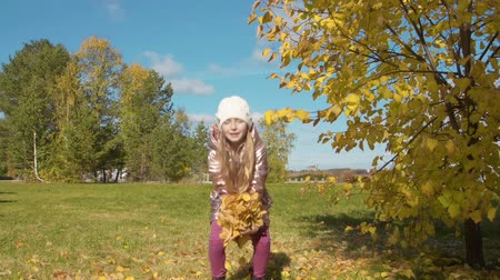 оставлять : Smiling teenager girl holding autumn leaves s and throwing up in autumn forest