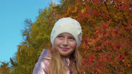 предподростковый : Cute blonde young girl in white hat standing in autumn park