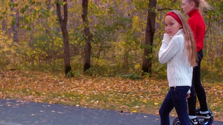 gyroscope : Teenager girls walking and riding on gyroscope on road in autumn park Stock Footage