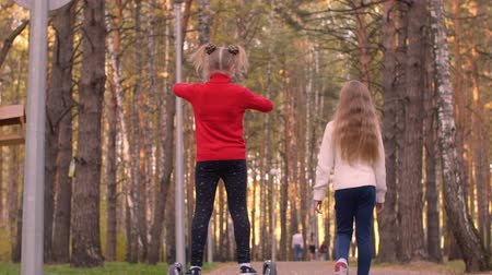 gyroscope : Happy teenager girls walking in autumn park and riding on gyroscope on pathway