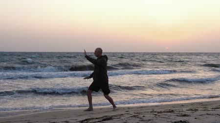 fegyelem : Man training Chinese martial art Taijiquan at sea beach, evening sky background