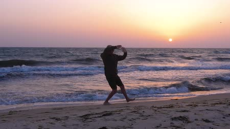 fegyelem : Man training Tai Chi chuan discipline outdoors at evening sea beach while sunset Stock mozgókép