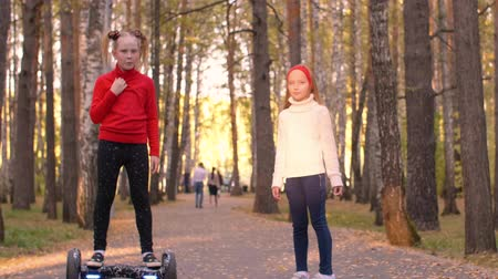 self balancing : Preteen girls walking with gyroscooter on road in autumn park with sunlight