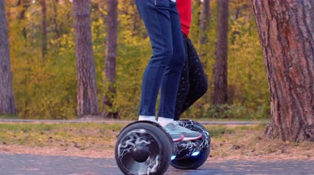 self balancing : Happy girl having ride on gyroscooter while holding hands with friends in park Stock Footage