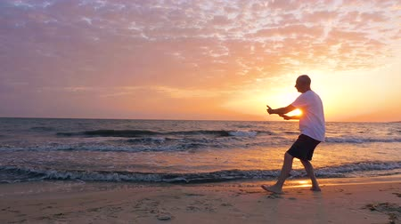 yin and yang : Man training Tai Chi chuan while morning sunrise in sky at sea beach Stock Footage