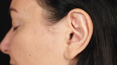 listener : Female left ear close up. Ear of adult brunette woman. Parts of face and body Stock Footage
