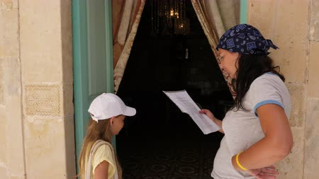 дверь : Mom reading information in paper to daughter teenager near door in home