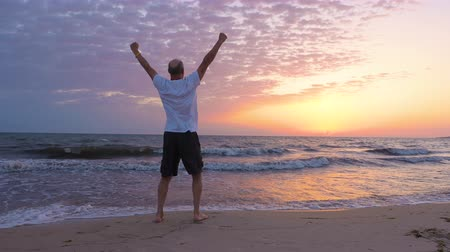 triunfar : Successful man rising hands and looking at sunrise on seascape