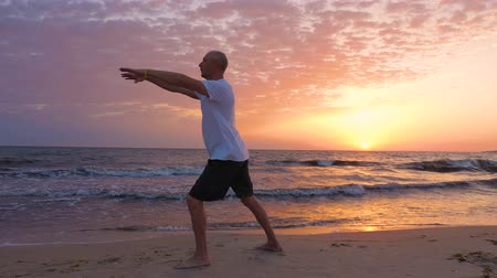 ostor : Sportive man practicing Tai Chi on seashore at sunrise