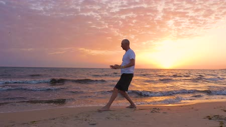 como : Athletic man practicing Tai Chi asian martial arts on sea beach in the morning