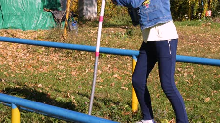 plac zabaw : Girl teenager walking on narrow crossbar with pole while obstacle course in park