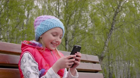 communion : Playful teenager girl using smart phone sitting on bench in spring city park