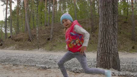 vest : Cheerful young girl dancing in forest outdoors in slow motion