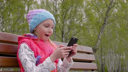 ławka : Excited young girl using phone while sitting on bench in park