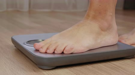 female measurements : Cropped shot of barefoot man checking weight on scale