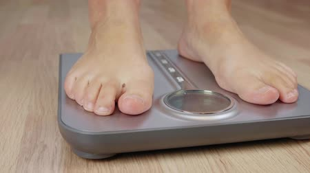 medir : Cropped shot of barefoot woman controlling his weight on scale Stock Footage
