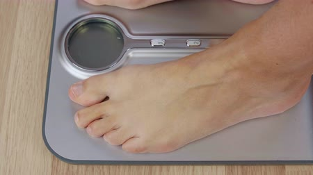 kilogramm : Close up human foot stepping on weighing scale for weight control Stock mozgókép