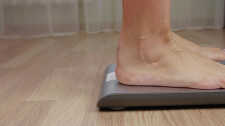 baixo teor de gordura : Legs of fitness women stepping to weighting scale for body mass control close up Stock Footage
