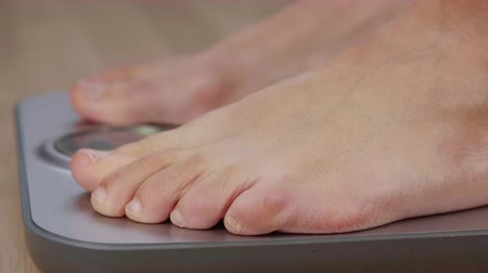 kilogramm : Human foot standing on weighing scale for body weight control close up