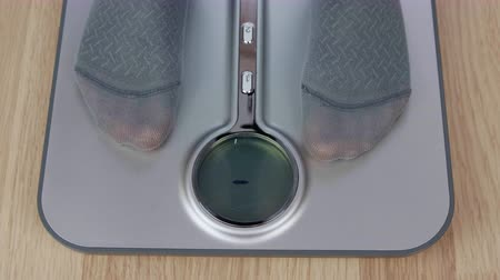baixo teor de gordura : Baby feet stepping on weight scale for body measuring close up Stock Footage