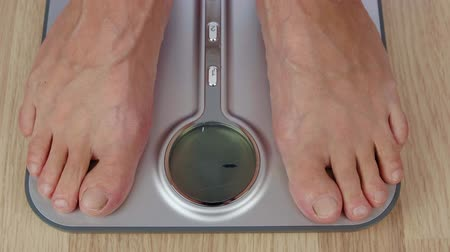 baixo teor de gordura : Close up male foot stepping on scale for weighting body top view Stock Footage