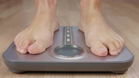 artış : Human foot stepping on weighting scale for body mass control while losing weight