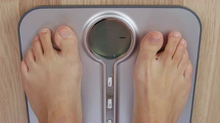 baixo teor de gordura : Top view human foot stepping on weighting scale for measuring body mass Stock Footage