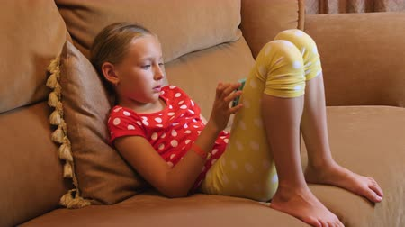 tendency : Teenager girl sitting on couch using mobile phone in living room interior
