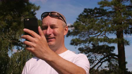 gadżety : Smiling man making photo or video with smartphone in nature
