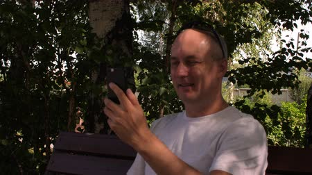 facetime : Positive man showing thumb up and waving while making video call on phone