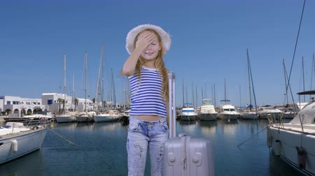 személyszállító hajó : Tourist girl with travel suitcase waiting ship in sea port on yacht background Stock mozgókép