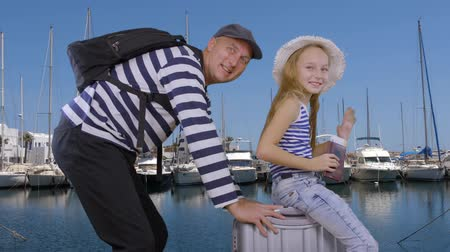 vztahy : Happy father together daughter sitting on suitcase go on sea cruise in sea port