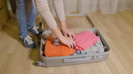 stuff bag : Woman putting stuff and clothes in travel suitcase on floor in home room Stock Footage