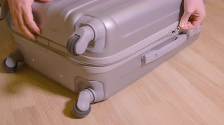 stuff bag : Close up female hand unzip fastener on travel suitcase on wooden floor in room