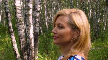 bétula : Attractive woman smiling and walking in birch grove in summer park. Profile view Vídeos