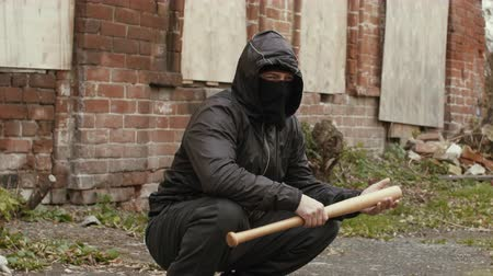 vandalismo : Bandit man in black mask and jacket with hood with baseball bat sits on street