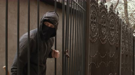 vandalismo : Bandit man in black mask and hood with baseball bat crawls through fence mesh