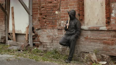 hostility : Hooligan in black mask and hood with baseball bat leaning back on brick wall