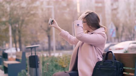 subscribers : Woman using mobile phone for selfie photo in social network on bench in city Stock Footage