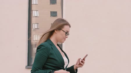 nem városi színhely : Smiling businesswoman in eyeglasses walking and using digital device outdoors